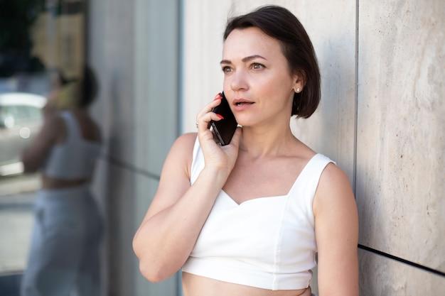 Zdziwienie dorosła kobieta w bieli rozmawia przez telefon i odwraca wzrok, stojąc na ulicy