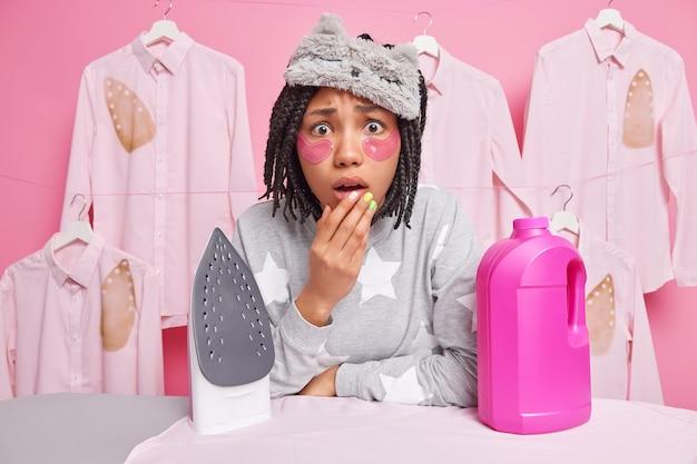 Zdziwiona afro amerykanka wygląda na zmartwioną kobietę w pobliżu detergentu i żelazka elektrycznego na desce do prasowania