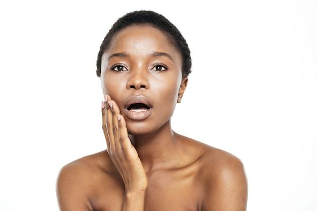 Zdziwiona afroamerykańska kobieta patrząca na kamerę na białym tle