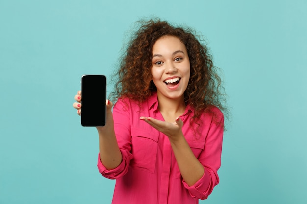 Zdziwiona afrykańska dziewczyna w ubranie wskazujące rękę na telefon komórkowy z pustym pustym ekranem na białym tle na tle niebieskiej ściany turkus. ludzie szczere emocje, koncepcja stylu życia. makieta miejsca na kopię.