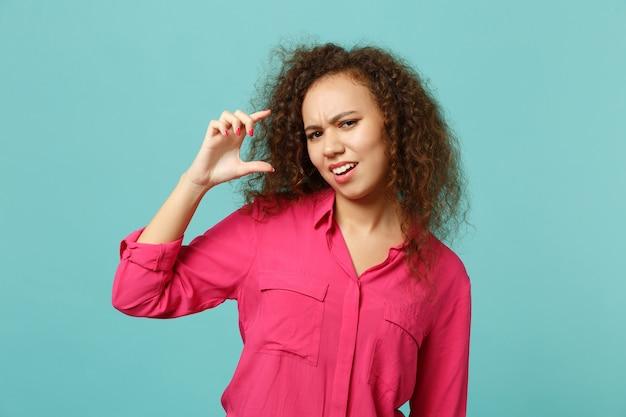 Zdziwiona afrykańska dziewczyna w zwykłych ubraniach, gestykulując, wykazując rozmiar z obszaru roboczego na białym tle na tle niebieskiej ściany turkus w studio. koncepcja życia szczere emocje ludzi. makieta miejsca na kopię.