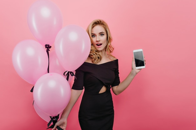 Zdziwiona, ale zadowolona młoda kobieta pozuje z nowym telefonem i imprezowymi balonami w wakacje. urocza blondynka z kręconymi fryzurami świętuje swoje urodziny.