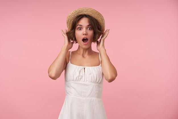Zdziwiona atrakcyjna młoda kobieta o krótkich brązowych włosach, patrząc szeroko otwartymi oczami i ustami, trzymając podniesione ręce na czapce marynarza stojąc