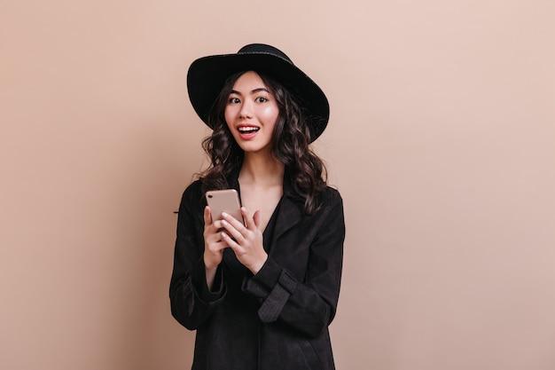 Zdziwiona azjatka trzymając smartfon i patrząc na kamery. elegancka kręcona kobieta w płaszczu z gadżetem.