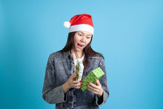 Zdziwiona azjatka w czapce świętego mikołaja otwiera prezent noworoczny