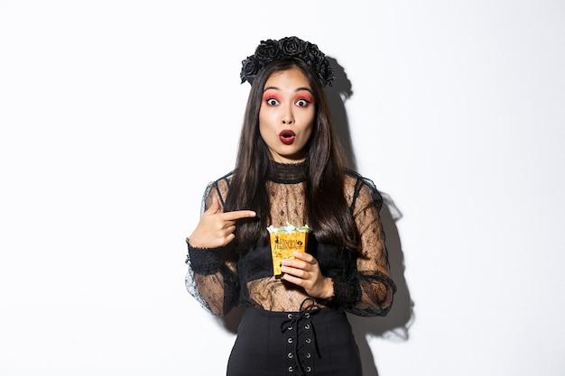Zdziwiona azjatycka dziewczyna patrząc na kamery, wskazując palcem na słodycze