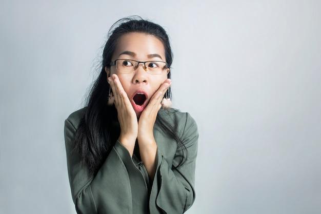 Zdziwiona azjatycka kobieta jest ubranym szkła na popielatym tle
