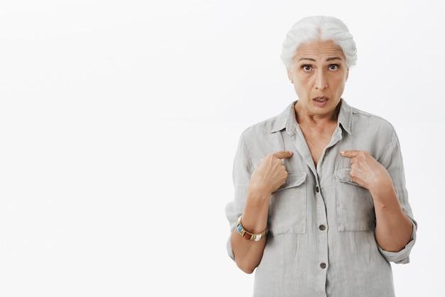 Zdziwiona babcia zadająca pytanie i wskazująca na siebie