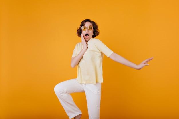 Zdziwiona biała kobieta w modnych żółtych okularach stojących na jasnej ścianie. zszokowana dziewczyna z falistymi brązowymi włosami dotyka jej twarzy podczas pozowania.