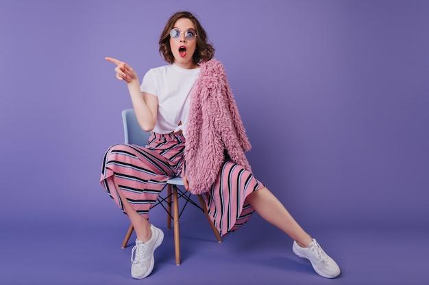 Zdziwiona biała kobieta w pasiastych spodniach siedzi na fioletowej ścianie z otwartymi ustami. kryty zdjęcie zdumiony kręcone dziewczyny w futrzanej kurtce, pozowanie na krześle.
