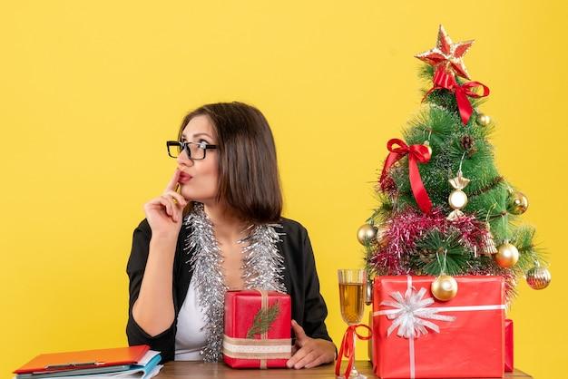 Zdziwiona biznesowa dama w garniturze w okularach trzymająca prezent, patrząc na coś i siedząca przy stole z choinką w biurze