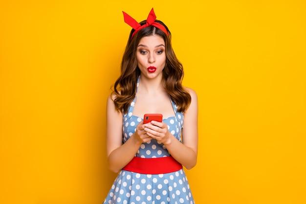 Zdziwiona blogerka dziewczyna używa krzyku telefonu komórkowego na żółtym tle