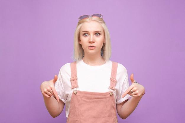 Zdziwiona blond kobieta w ślicznych ubraniach pokazując palce w dół