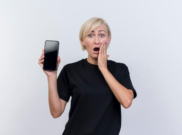 Zdziwiona blond słowiańska kobieta w średnim wieku pokazująca telefon komórkowy trzymając rękę na policzku patrząc na kamerę na białym tle z miejsca na kopię