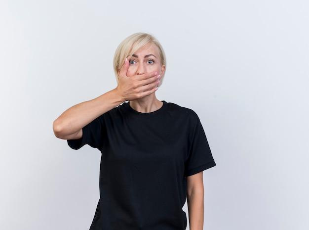 Zdziwiona blond słowiańska kobieta w średnim wieku, trzymając rękę na ustach, patrząc na kamery na białym tle na białym tle z miejsca na kopię
