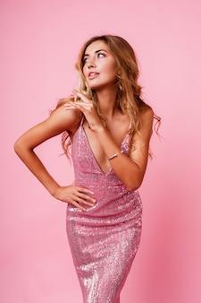 Zdziwiona blondynka z wietrznymi włosami pozowanie. różowa ściana. wspaniały model. ekstatyczne emocje.