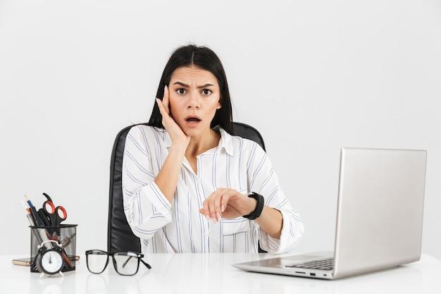 Zdziwiona brunetka businesswoman patrząc na zegarek siedząc przy stole z papeterią i pracując na laptopie w biurze odizolowane na białej ścianie