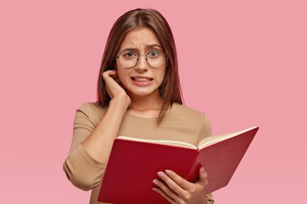 Zdziwiona brunetka nauczycielka trzyma otwartą książkę z przodu