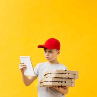 Zdziwiona chłopiec trzyma notepad kopii przestrzeń