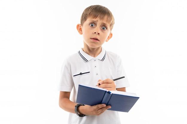 Zdziwiona chłopiec z książką i piórem na bielu