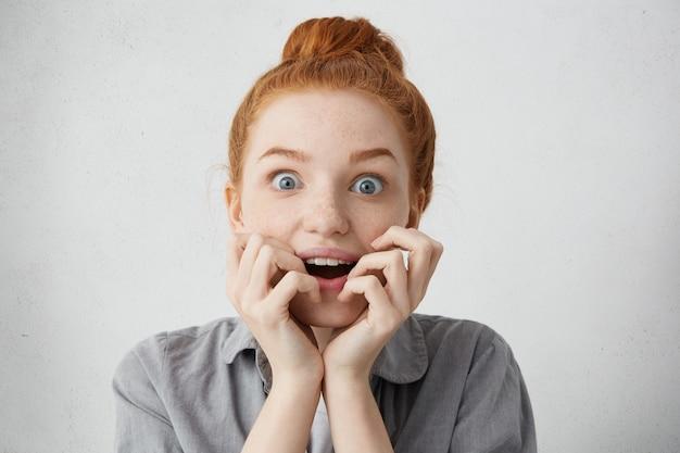 Zdziwiona, ciekawa, młoda kaukaska rudowłosa kobieta, patrząca z zafascynowanymi oczami i szeroko otwartymi ustami, trzymająca się za twarz podczas słuchania historii z zainteresowaniem i oczekiwaniem