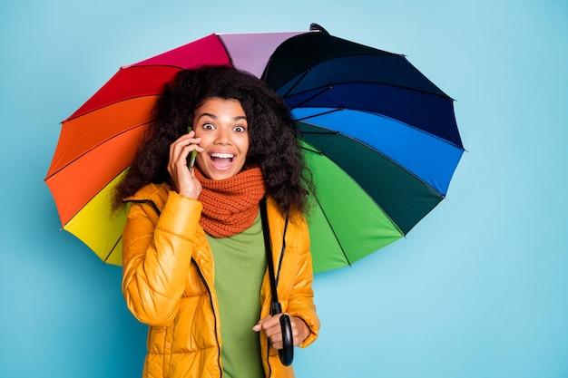 Zdziwiona ciemnoskóra dama z telefonem parasolowym rozmawia przez telefon komórkowy na niebieskim tle