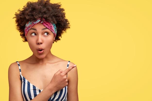 Zdziwiona ciemnoskóra młoda kobieta ma kręconą fryzurę, otwiera usta ze zdumienia, wskazuje w prawym górnym rogu, demonstruje coś niewiarygodnego