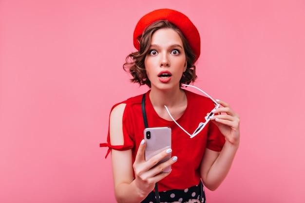 Zdziwiona ciemnowłosa dziewczyna pozuje z telefonem. dobrze ubrana młoda dama w berecie wyrażająca zdziwienie.