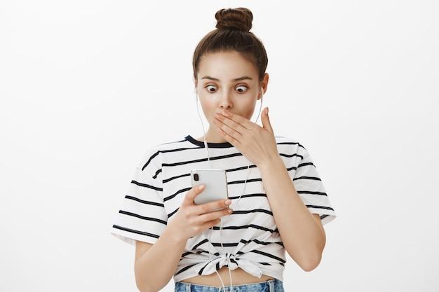 Zdziwiona dziewczyna dysząc, wpatruje się w smartfon z zszokowaną twarzą, nosi słuchawki