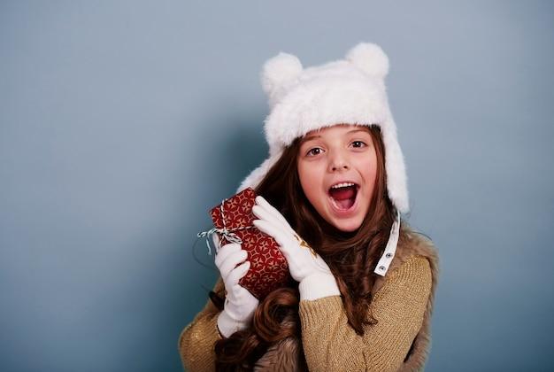 Zdziwiona dziewczyna korzystających z prezentem na boże narodzenie