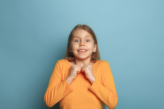 Zdziwiona dziewczyna na niebieskim tle studio. wyraz twarzy i koncepcja emocji ludzi.