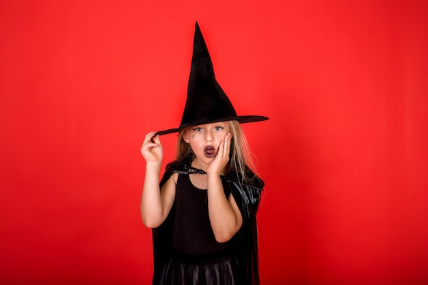 Zdziwiona dziewczyna na obrazku czarownicy w kapeluszu na halloween na czerwonej ścianie na białym tle z kopią miejsca