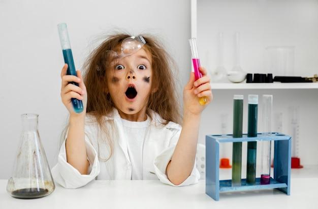 Zdziwiona dziewczyna naukowiec w laboratorium z probówkami i nieudany eksperyment