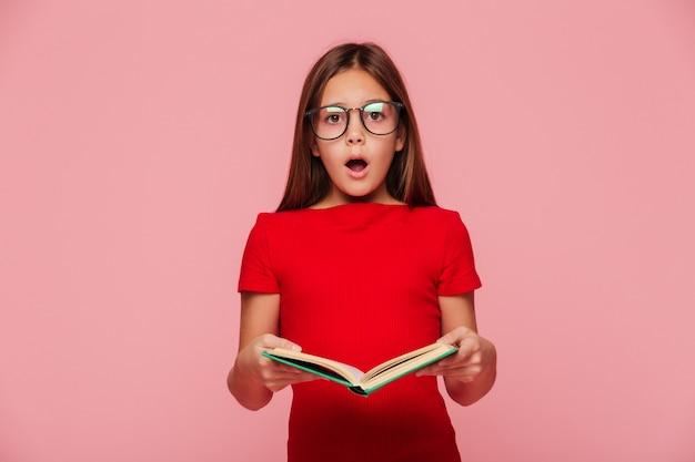 Zdziwiona dziewczyna nerd patrząc podczas czytania książki
