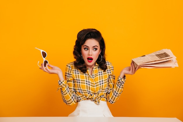 Zdziwiona dziewczyna pinup trzymając okulary na żółtym tle. elegancka młoda kobieta pozuje z gazetą.