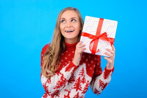 Zdziwiona dziewczyna próbuje odgadnąć, co jest zapakowane w pudełko