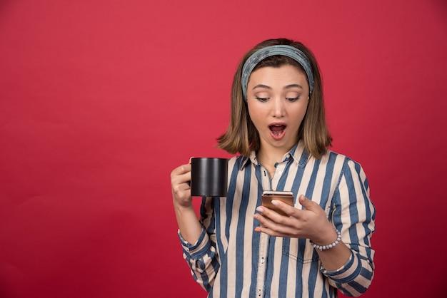 Zdziwiona dziewczyna sprawdzanie telefonu komórkowego z filiżanką herbaty