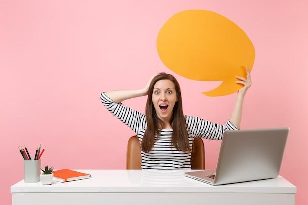 Zdziwiona dziewczyna trzyma żółty pusty pusty say chmura dymek pracy na białym biurku z laptopem pc na białym tle na pastelowym różowym tle. koncepcja kariery biznesowej osiągnięcia. skopiuj miejsce na reklamę.
