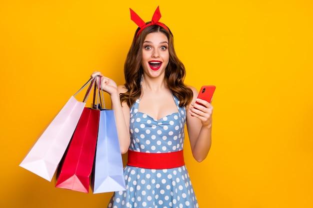 Zdziwiona dziewczyna używa smartfona trzymając torby na zakupy w niebieskiej sukience w kropki