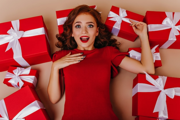 Zdziwiona dziewczyna w czerwonej sukience na podłodze w pobliżu prezentów. zadowolony biały modelka zabawy w urodziny.