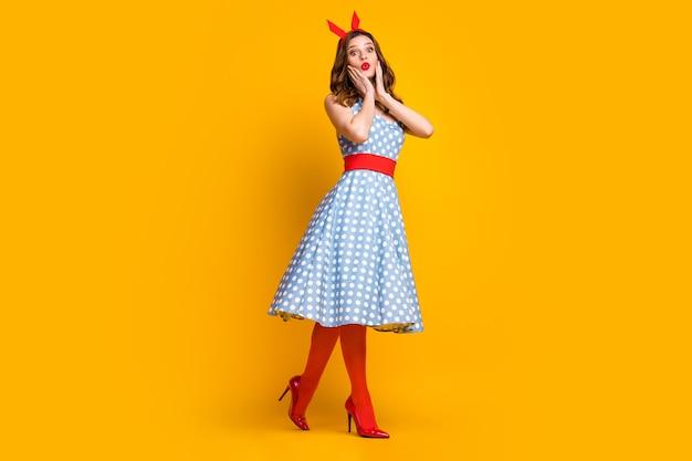 Zdziwiona dziewczyna w kropkowanej niebieskiej sukience przejść na żółtym tle