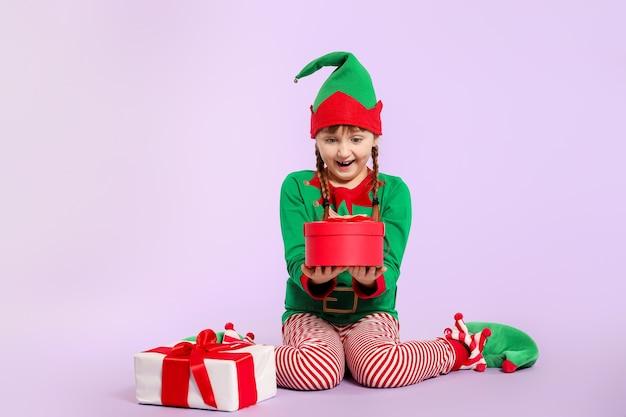 Zdziwiona dziewczyna w stroju elfa i prezenty na kolorowej powierzchni