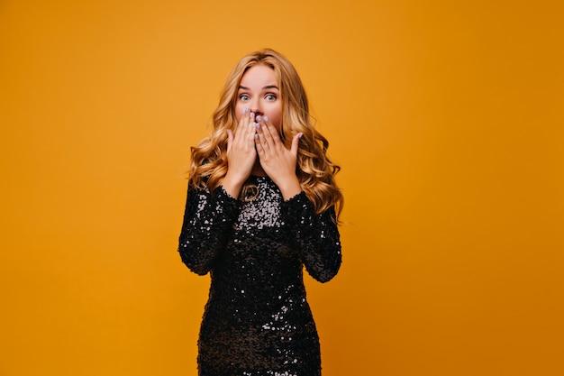 Zdziwiona dziewczyna w stroju partii, zakrywając usta rękami. słodka zaskoczona pani w czarnej sukience.