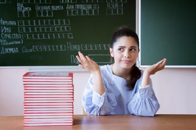Zdziwiona dziewczyna w szkłach siedzi przeciw blackboard w sala lekcyjnej