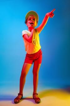 Zdziwiona dziewczyna, wskazując na białym tle na niebieskiej ścianie