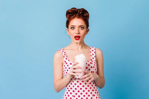 Zdziwiona dziewczyna z czerwonymi ustami pije koktajl mleczny. studio strzałów emocjonalnej młodej damy w sukience w kropki, stojącej na niebieskiej przestrzeni.