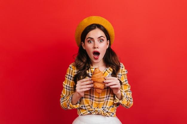 Zdziwiona dziewczyna z falowanymi włosami, trzymając pyszną bułkę. zielonooka kobieta w żółtym stroju chce zjeść rogalika.