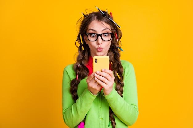 Zdziwiona dziewczyna z ołówkową fryzurą przeczytała informacje na smartfonie na białym tle na żółtym tle