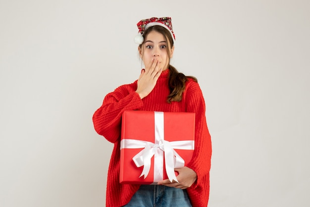 Zdziwiona dziewczyna z santa hat trzyma obecny wkładając dłoń do ust stojąc na białym