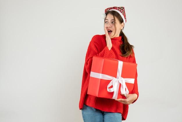 Zdziwiona dziewczyna z santa hat trzyma prezent na białym tle